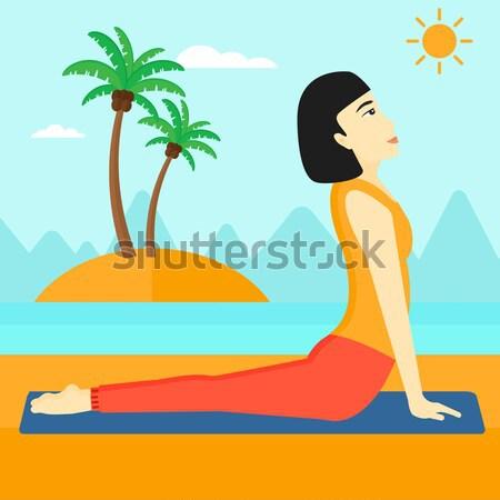 Woman practicing yoga upward dog pose on beach. Stock photo © RAStudio