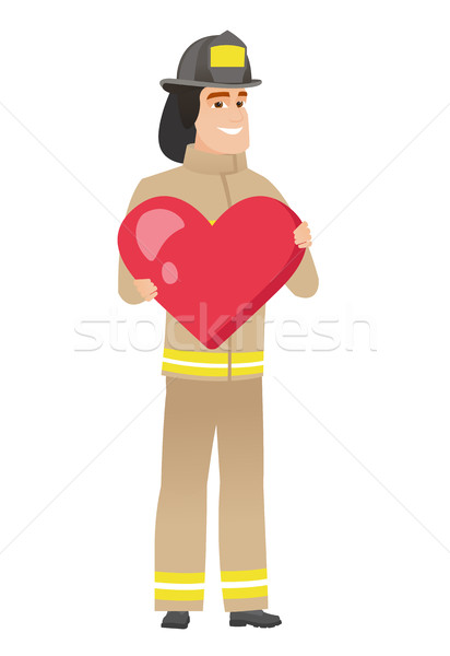 Stock photo: Caucasian firefighter holding a big red heart.