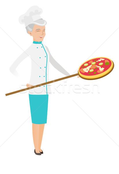 Senior caucasian chef preparing pizza. Stock photo © RAStudio