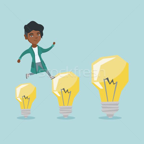 African business woman jumping on light bulbs. Stock photo © RAStudio