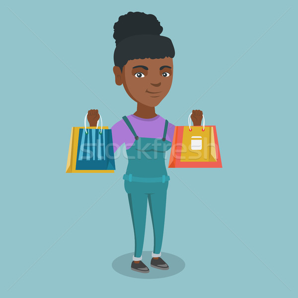 Young african-american woman holding shopping bags Stock photo © RAStudio