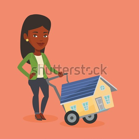 Young african woman with a house on a trolley. Stock photo © RAStudio