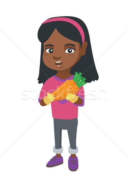 African-american girl holding fresh carrot. Stock photo © RAStudio