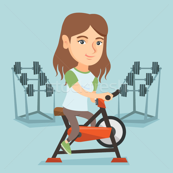 Young caucasian woman riding stationary bicycle. Stock photo © RAStudio