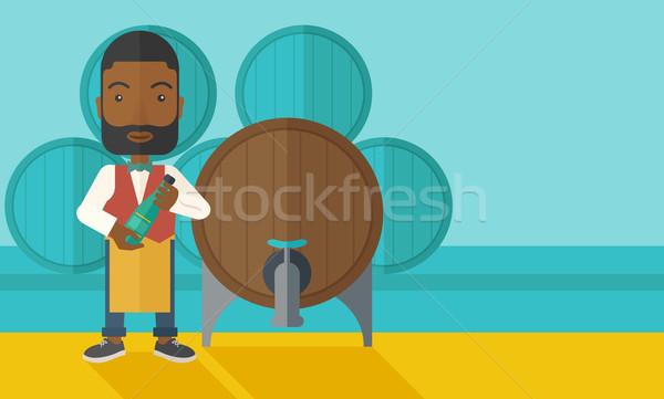 African Wine maker inspecting wine from barrel. Stock photo © RAStudio