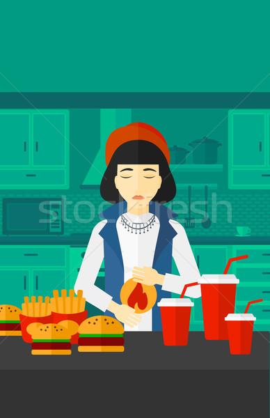 Donna sofferenza bruciore di stomaco asian piedi tavolo da cucina Foto d'archivio © RAStudio