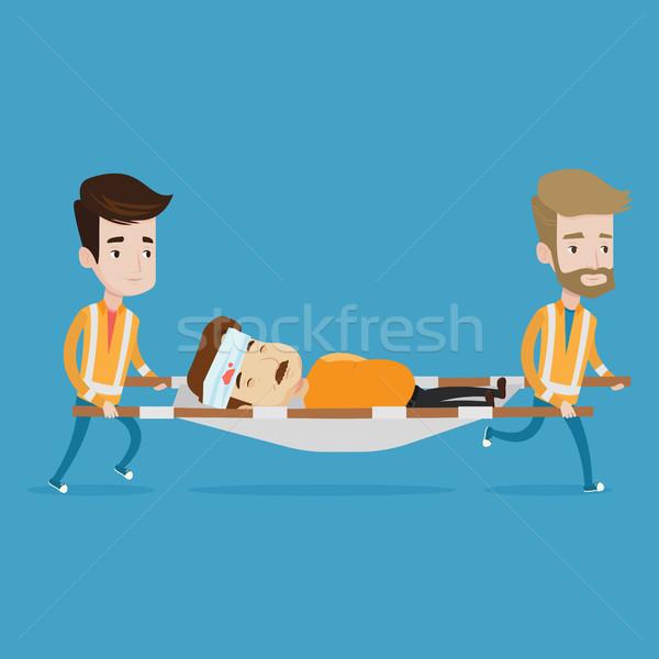 Emergency doctors carrying man on stretcher. Stock photo © RAStudio