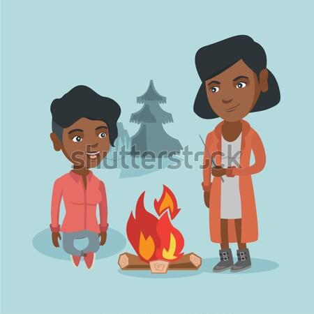 Two friends sitting around bonfire in camping. Stock photo © RAStudio