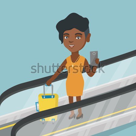 Stock photo: Woman using smartphone on escalator in airport.