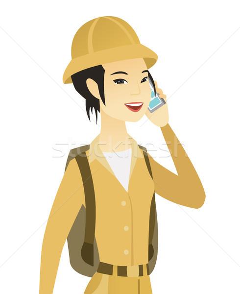 Jovem asiático viajante falante telefone móvel sorridente Foto stock © RAStudio