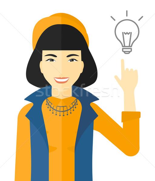 Woman pointing at light bulb. Stock photo © RAStudio