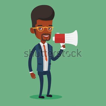 Young man speaking into megaphone. Stock photo © RAStudio