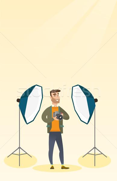 Photographer with a camera in a photo studio. Stock photo © RAStudio