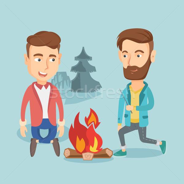 Dos amigos sesión alrededor hoguera camping Foto stock © RAStudio