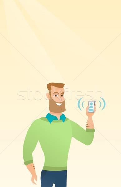 Young caucasian man holding ringing mobile phone. Stock photo © RAStudio