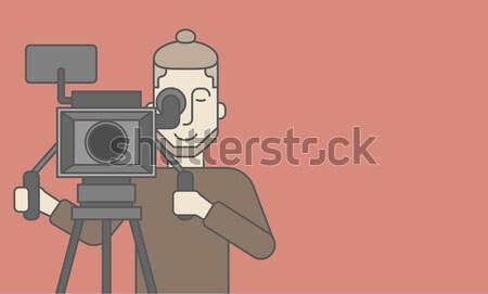 Cameraman with beard looking through movie camera Stock photo © RAStudio
