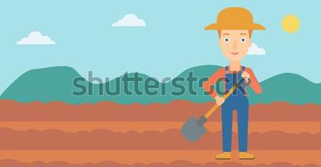 Farmer on the field with shovel. Stock photo © RAStudio