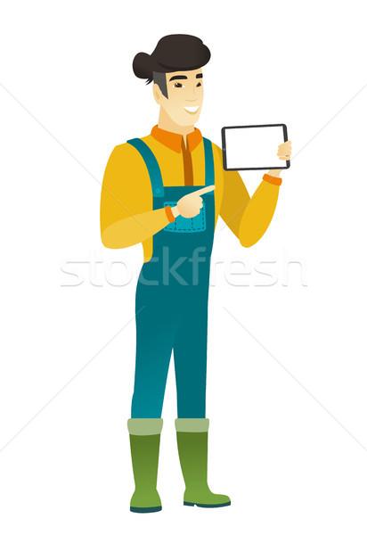 Smiling farmer holding tablet computer. Stock photo © RAStudio
