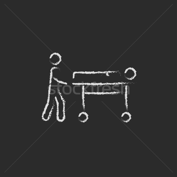 Stock photo: Man pushing stretchers icon drawn in chalk.