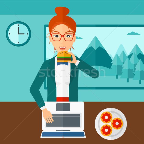 Mulher alimentação hambúrguer em pé quarto laptop Foto stock © RAStudio