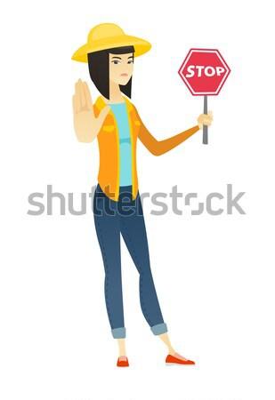 Asian traveler holding stop road sign. Stock photo © RAStudio