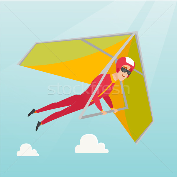 Young caucasian man flying on hang-glider. Stock photo © RAStudio
