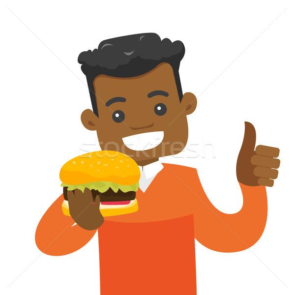 Jóvenes hombre comer hamburguesa alegre Foto stock © RAStudio