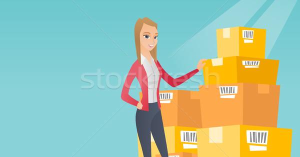 Business woman checking boxes in warehouse. Stock photo © RAStudio