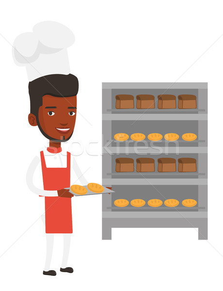 Happy young male baker holding tray of bread. Stock photo © RAStudio