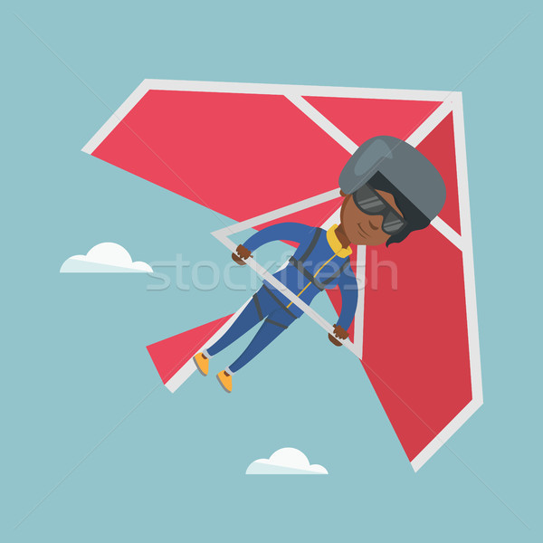 Stock photo: Young african-american woman flying on hang-glider