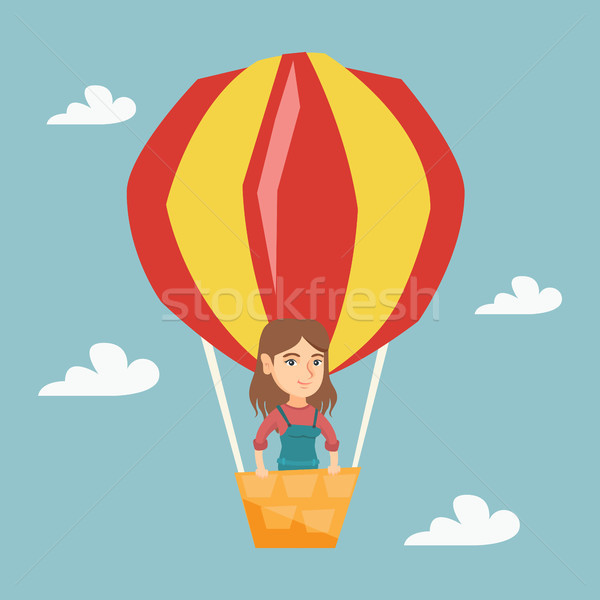 Young caucasian woman flying in hot air balloon. Stock photo © RAStudio