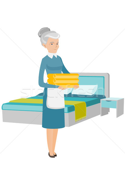 Caucasian housekeeping maid with stack of linen. Stock photo © RAStudio