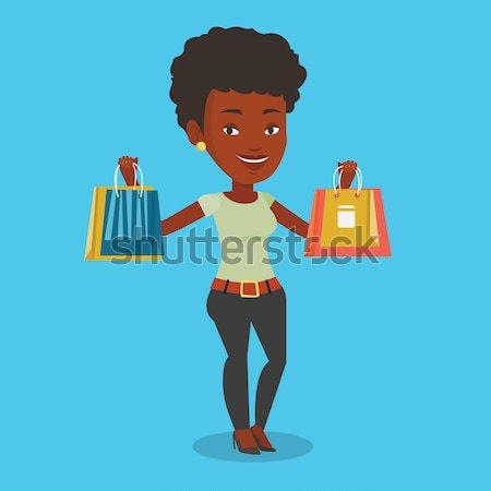 Happy woman holding shopping bags. Stock photo © RAStudio