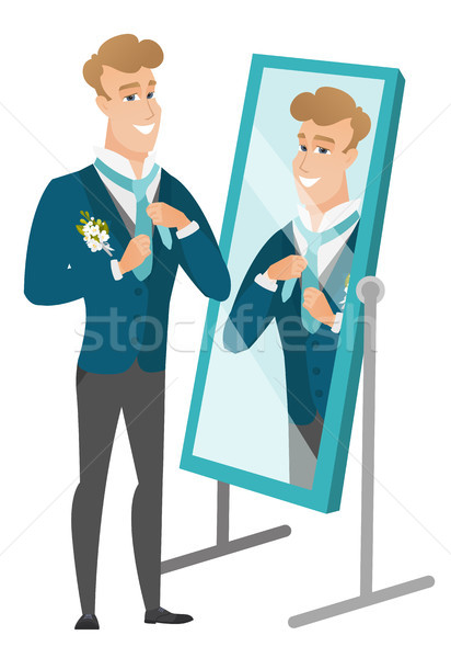 Groom looking in the mirror and adjusting tie. Stock photo © RAStudio