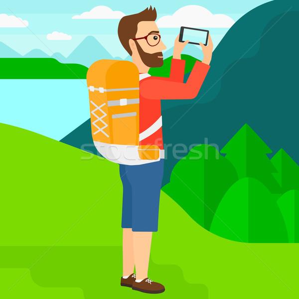 Backpacker taking photo. Stock photo © RAStudio