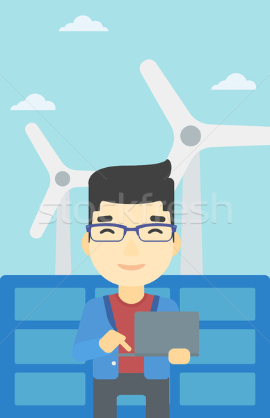 Man checking solar panels and wind turbines. Stock photo © RAStudio