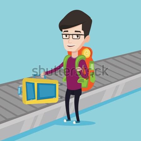 Man picking up suitcase on luggage conveyor belt Stock photo © RAStudio