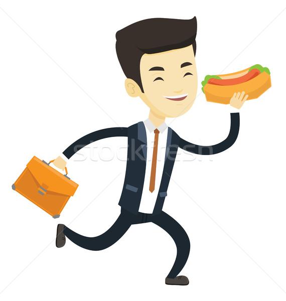 Homme d'affaires manger hot dog asian dépêchez serviette Photo stock © RAStudio