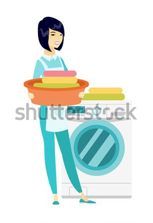 Senior housewife using washing machine at laundry. Stock photo © RAStudio