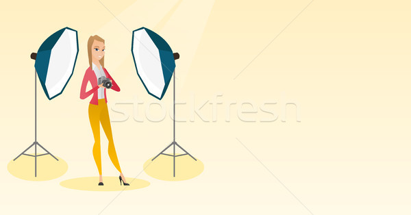 Photographer with a camera in a photo studio. Stock photo © RAStudio