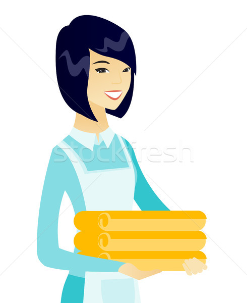 Young asian housekeeping maid with stack of linen. Stock photo © RAStudio