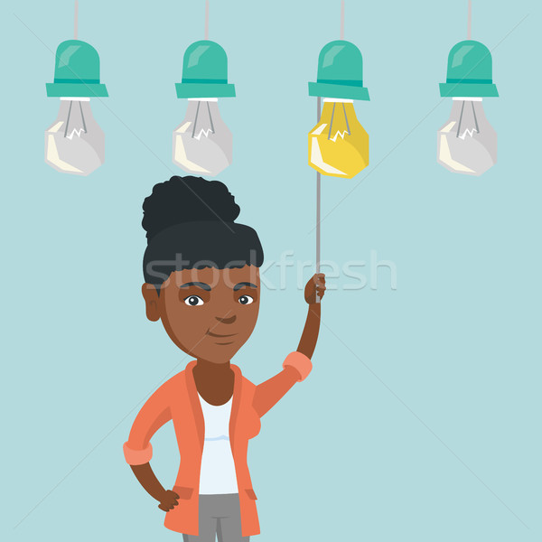 Business woman switching on hanging idea bulb. Stock photo © RAStudio