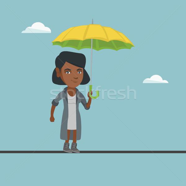 African business woman balancing on a tightrope. Stock photo © RAStudio