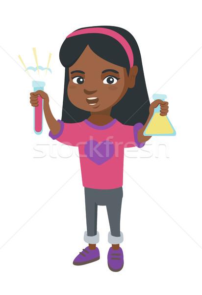 Little african girl holding test tube and beaker. Stock photo © RAStudio