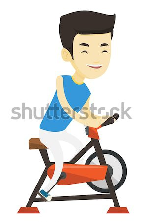 Young woman riding stationary bicycle. Stock photo © RAStudio