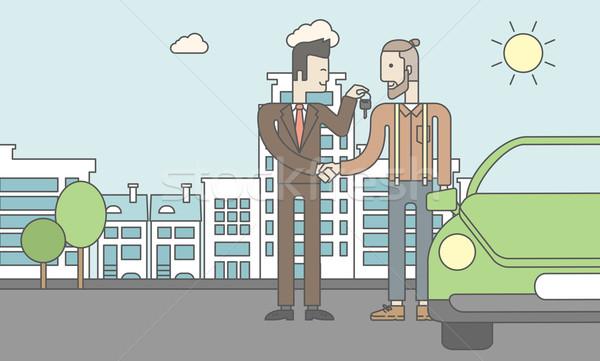 Car salesman giving the car keys to a new owner  Stock photo © RAStudio
