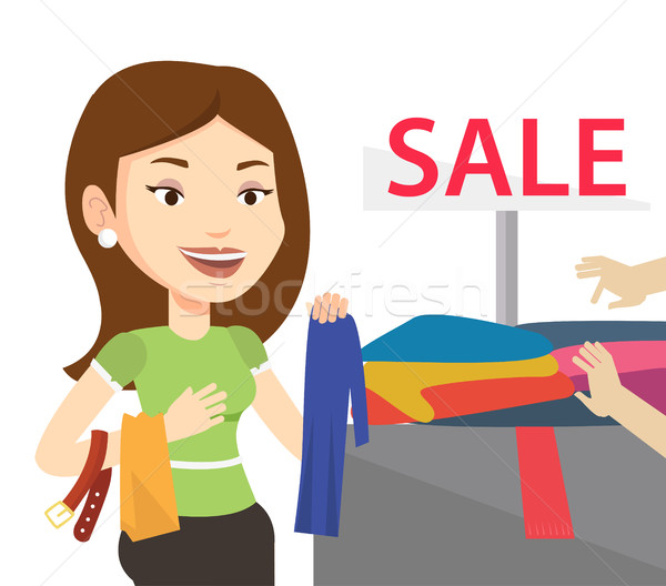 Stock photo: Young woman choosing clothes in shop on sale.