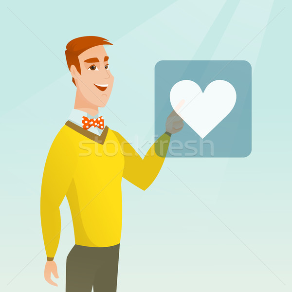 Young man pressing heart shaped button. Stock photo © RAStudio