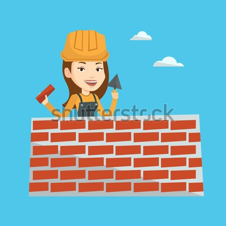 Young bricklayer working with spatula and brick. Stock photo © RAStudio