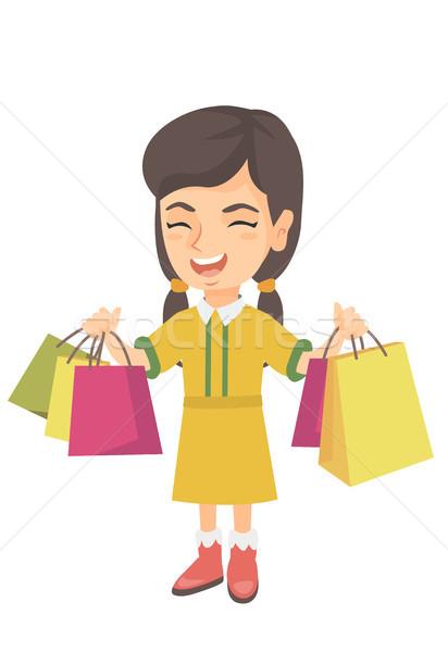 Happy caucasian girl holding shopping bags. Stock photo © RAStudio